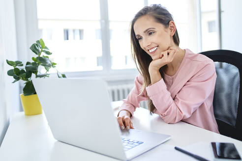 Happy young businesswoman working with laptop in office - BSZF01529