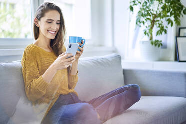 Smiling young woman sitting on sofa with smartphone and cup of coffee - BSZF01535