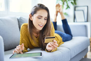 Beautiful smiling woman buying online using tablet and credit card - BSZF01538