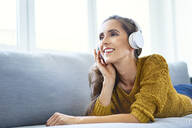 Happy young woman listening to music with headphones while lying on sofa - BSZF01544