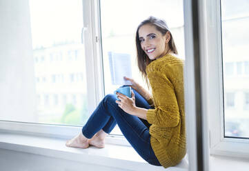 Young woman sitting on windowsill with book and cup of tea looking at camera - BSZF01550