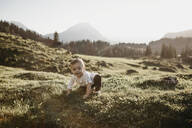 Happy little boy crawling on an alpine meadow, Schwaegalp, Nesslau, Switzerland - LHPF01094