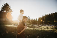 Father carrying little son on shoulders on a hiking trip at sunset, Schwaegalp, Nesslau, Switzerland - LHPF01106