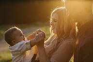 Happy family with little son outdoors at sunset - LHPF01118