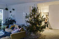 Woman at home with decorated pine Christmas tree in living room - MFF04862