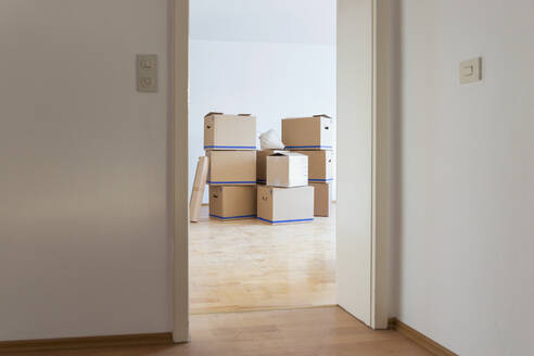 Cardboard boxes in an empty room in a new home - MAMF00793