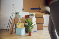 Woman carrying cardboard box in a new home - MAMF00796