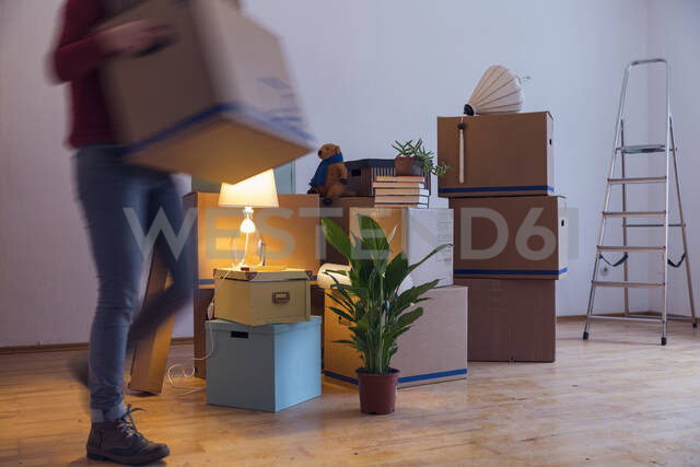 Woman carrying cardboard box in a new home - MAMF00799 - Maria Maar/Westend61