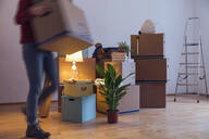 Woman carrying cardboard box in a new home - MAMF00799