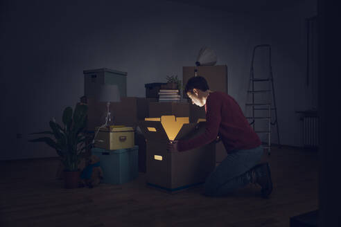 Woman looking into shining cardboard box in a new home - MAMF00805