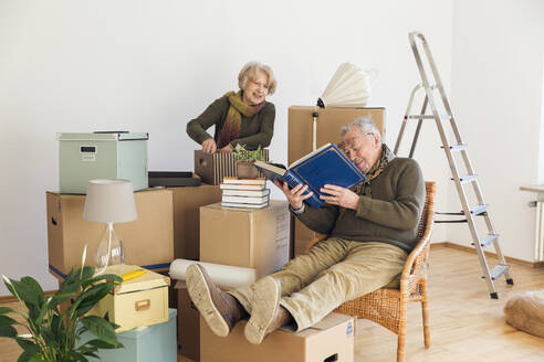 Senior couple with photo album surrounded by cardboard boxes in an empty room - MAMF00814