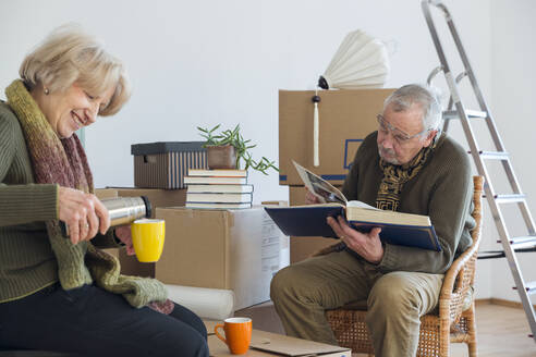 Senior couple with photo album and hot drink surrounded by cardboard boxes in an empty room - MAMF00817