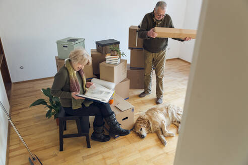 Senior couple with dog surrounded by cardboard boxes in an empty room - MAMF00820