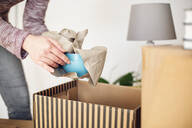 Close-up of woman unpacking cardboard box in new home taking out bowl - MAMF00835