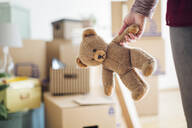 Close-up of woman holding teddy bear in new home - MAMF00838