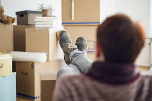 Woman relaxing surrounded by cardboard boxes in a new home - MAMF00841