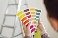 Woman holding colour sample in an empty room with a ladder - MAMF00844