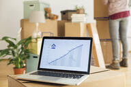 Rising line graph on laptop screen in front of cardboard boxes in a new home - MAMF00847