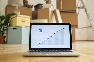 Rising line graph on laptop screen in front of cardboard boxes in an empty room in a new home - MAMF00850