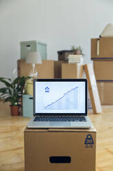 Rising line graph on laptop screen in front of cardboard boxes in an empty room in a new home - MAMF00853