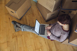 Woman using laptop with rising line graph on the screen in a new home - MAMF00856