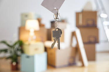 House key in front of cardboard boxes in an empty room in a new home - MAMF00859