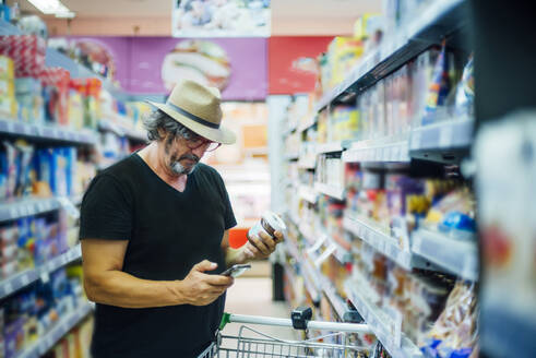 Senior man shopping in a supermarket using his smartphone - CJMF00117