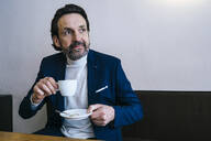 Portrait of mature businessman with cup of coffee in a cafe - JLOF00324