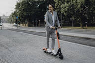 Businessman with e-scooter in the city - JLOF00354