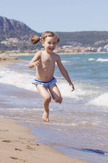 Portrait of happy little girl jumping in the air on the beach, Girona, Spain - XCF00279