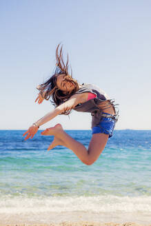 Girl jumping in the air at seafront - XCF00282