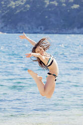 Portrait of girl jumping in the air in front of the sea - XCF00285