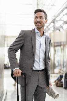 Portrait of smiling businessman with baggage - DIGF08441