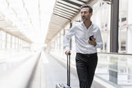 Businessman on moving walkway at the airport - DIGF08459