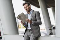 Portrait of businessman reading newspaper outdoors - DIGF08495