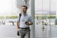 Businessman with cell phone and earphones on the go - DIGF08501