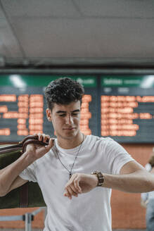 Young man checking the time at train station - JMHMF00019