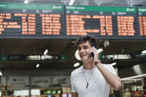 Young man waiting at train station and using smartphone - JMHMF00022