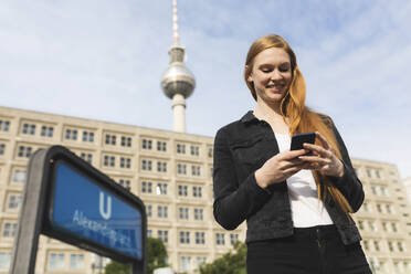 Portrait of smiling young woman at Alexanderplatz looking at cell phone, Berlin, Germany - WPEF01998