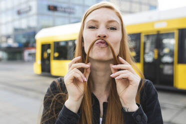 Portrait of redheaded young woman making mustache with her hair, Berlin, Germany - WPEF02001