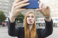Portrait of redheaded young woman pouting mouth while taking selfie with smartphone, Berlin, Germany - WPEF02004