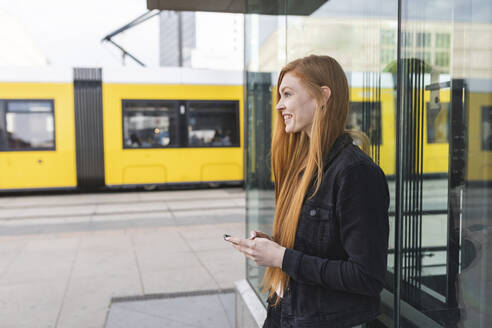 Redheaded young woman with smartphone in the city, Berlin, Germany - WPEF02007