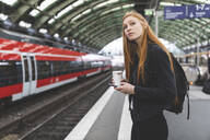 Portrait of redheaded young woman  with smartphone and coffee to go waiting at platform, Berlin, Germany - WPEF02010