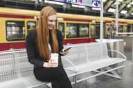 Redheaded young woman with coffee to go waiting at platform using smartphone, Berlin, Germany - WPEF02013