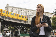 Portrait of redheaded young woman with smartphone in the city, Berlin, Germany - WPEF02016
