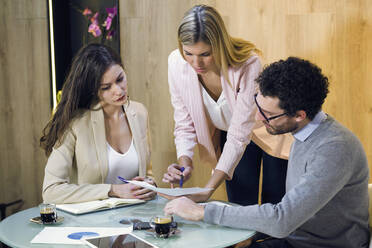 Three business people having a meeting in modern office discussing document - JSRF00681