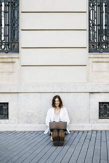 Businesswoman sitting on ground in the city, using laptop - JRFF03765
