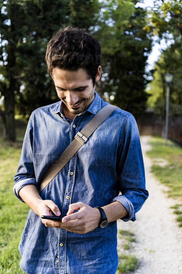 Smiling man using his smartphone - GIOF07170 - Giorgio Fochesato/Westend61
