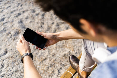 Close-up of man sitting on a park bench using his smartphone - GIOF07173