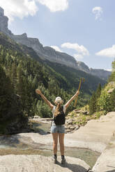 Rear view of happy woman enjoying the view in the mountains, Ordesa national park, Aragon, Spain - AHSF00851